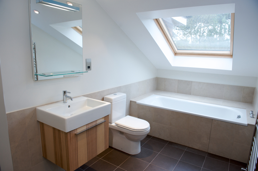 Bathroom conversion built into the eaves of a house with roof windows providing light.